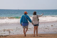 Senior citizen baby boomer male and female caucasian couple walking on the beach towards the ocean holding hands and pointing. stock photography