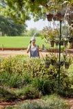 Senior citizen Caucasian Female watering trop Stock Images