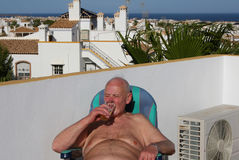 Senior citizen chilling out with a nice cold beer. Grandad chilling out in the sun on a villa rooftop veranda with a nice cold beer whilst on holiday in Spain Royalty Free Stock Photos