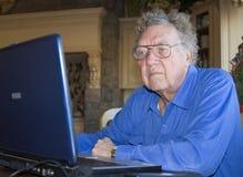 Senior citizen on computer. Senior citizen is working on laptop computer royalty free stock photo