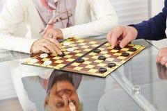 Senior citizen couple playing. Happy senior citizen couple playing checkers at home stock photos