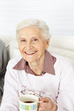 Senior citizen with cup of coffee. Happy senior citizen with a hot cup of coffee in the morning royalty free stock image