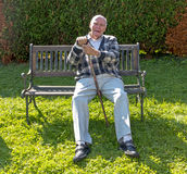 Senior citizen enjoys sitting on a bench in his garden Royalty Free Stock Images