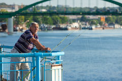 Senior citizen fishing from the dock Stock Photo