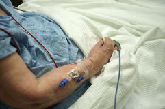 Senior Citizen get IV in forearm. Senior citizen waiting to receive medication via IV inserted in forearm Stock Photos