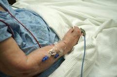 Senior Citizen get IV in forearm. Senior citizen waiting to receive medication via IV inserted in forearm stock photos