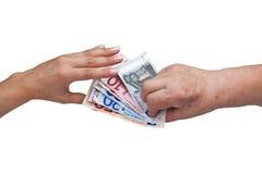 Senior citizen gives young woman money Stock Photography