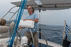 Senior Citizen at the helm of a sailboat stock photography