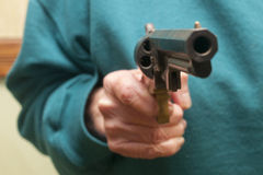 Senior Citizen Holding A Gun. An elderly woman holding a gun Royalty Free Stock Photo