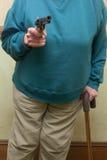 Senior Citizen Holding A Gun. An elderly woman holding a gun Royalty Free Stock Image