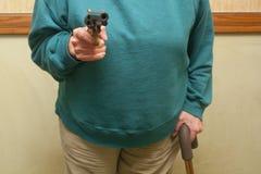 Senior Citizen Holding A Gun. An elderly woman holding a gun Stock Photos