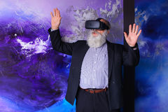 Senior citizen immersed in virtual reality with help of special Stock Photography