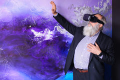 Senior citizen immersed in virtual reality with help of special. Elderly man in VR glasses outside imagination felt virtual reality and enjoys seen and new Royalty Free Stock Photo
