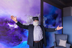 Senior citizen immersed in virtual reality with help of special Royalty Free Stock Photo