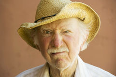 Senior Citizen Man in a Cowboy Hat. Senior Citizen Man Frowning n a Straw Cowboy Hat Stock Image
