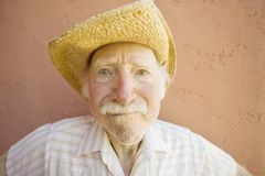 Senior Citizen Man in a Cowboy Hat. Senior Citizen Man with a Funny Expression Wearing a Straw Cowboy Hat Royalty Free Stock Photo
