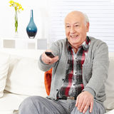 Senior citizen man watching TV. Happy senior citizen man watching TV with remote control stock images