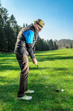 Senior citizen is playing golf. Active retirement. A man is golfing to stay in shape. On green grass with woods in the background stock images