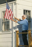 Senior citizen raising the American flag on house in Stonington, Maine Stock Photos