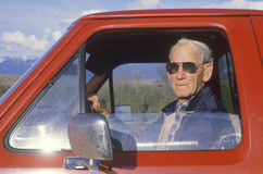 A senior citizen in a red pickup truck,. National Bison Range, MT Stock Photos