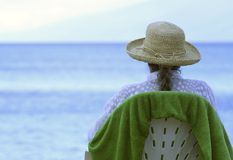 Senior Citizen Relaxing on the Beach. A senior citizen woman sitting on a chair at the beach wearing a hat Stock Image