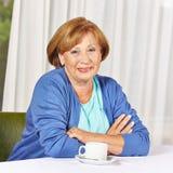 Senior citizen sitting at coffee. Smiling female senior citizen sitting at coffee table in retirement home stock photos