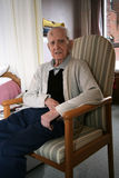 Senior citizen sitting idle. A senior citizen sits idle in his room in a long term care facility stock photo