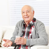 Senior citizen taking medical pill. Senior citizen at home taking medical pill with cup of water stock photos