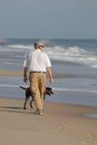 Senior citizen walking beach. With his dog royalty free stock image