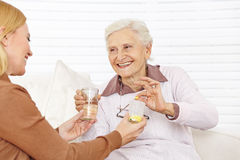 Senior citizen woman getting. Senior citizen women getting medical pill with water in a retirement home royalty free stock photography