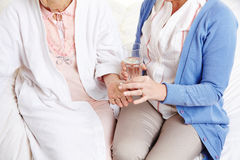 Senior citizen woman getting pill. Senior citizen women getting pill with water from a nurse royalty free stock image