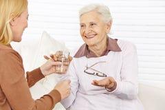 Senior citizen woman taking medical. Smiling senior citizen women taking medical pill with a cup of water royalty free stock image