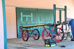 Senior citizen working on retro cart in train station, FL Stock Photo