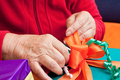 Senior citizen wrap or unpack gifts, closeup Royalty Free Stock Photography