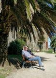 Senior citizens on bench in sunshine Stock Photos