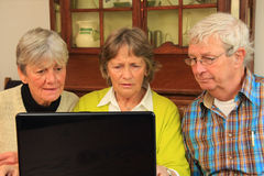 Senior citizens and the internet. Three active senior citizens surfing the internet Stock Photo