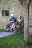 Senior citizens resting and making cell phone call on Plaza Mayor, in Ainsa, Huesca, Spain in Pyrenees Mountains, an old walled to Stock Photo