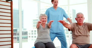 Senior citizens working out with physiotherapist stock video