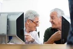 Senior Classmates Talking At Computer Desk In Classroom Stock Photos