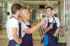 Senior cleaner explaining job to younger coleagues Stock Photo