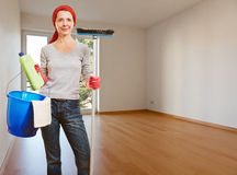 Senior cleaning lady in empty. Senior cleaning lady with cleaning products standing in an empty apartment room royalty free stock photos