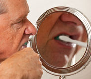 Senior cleaning teeth stock photo