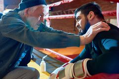 Senior Coach Motivating Young Fighter. Side view  portrait of senior coach shaking young professional fighter in corner of boxing ring giving pep talk, copy Royalty Free Stock Photos