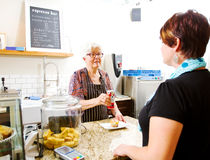 Senior in coffee shop serving customer Stock Image