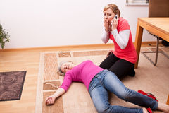 Senior collapsed young woman calling help Royalty Free Stock Photography