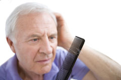 senior combing hair, hair falling out in comb, cut out Royalty Free Stock Photos