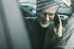 Senior commuter travelling by a taxi and making phone call Royalty Free Stock Photos