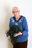 Senior confused with tangled christmas lights Stock Photo