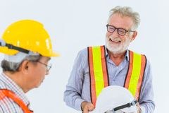 Senior construction engineers worker talking together happy smile working. Mix race senior construction engineers worker talking together happy smile working royalty free stock photography