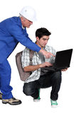 Senior construction worker and apprentice. A senior construction worker and his apprentice using a laptop stock photography